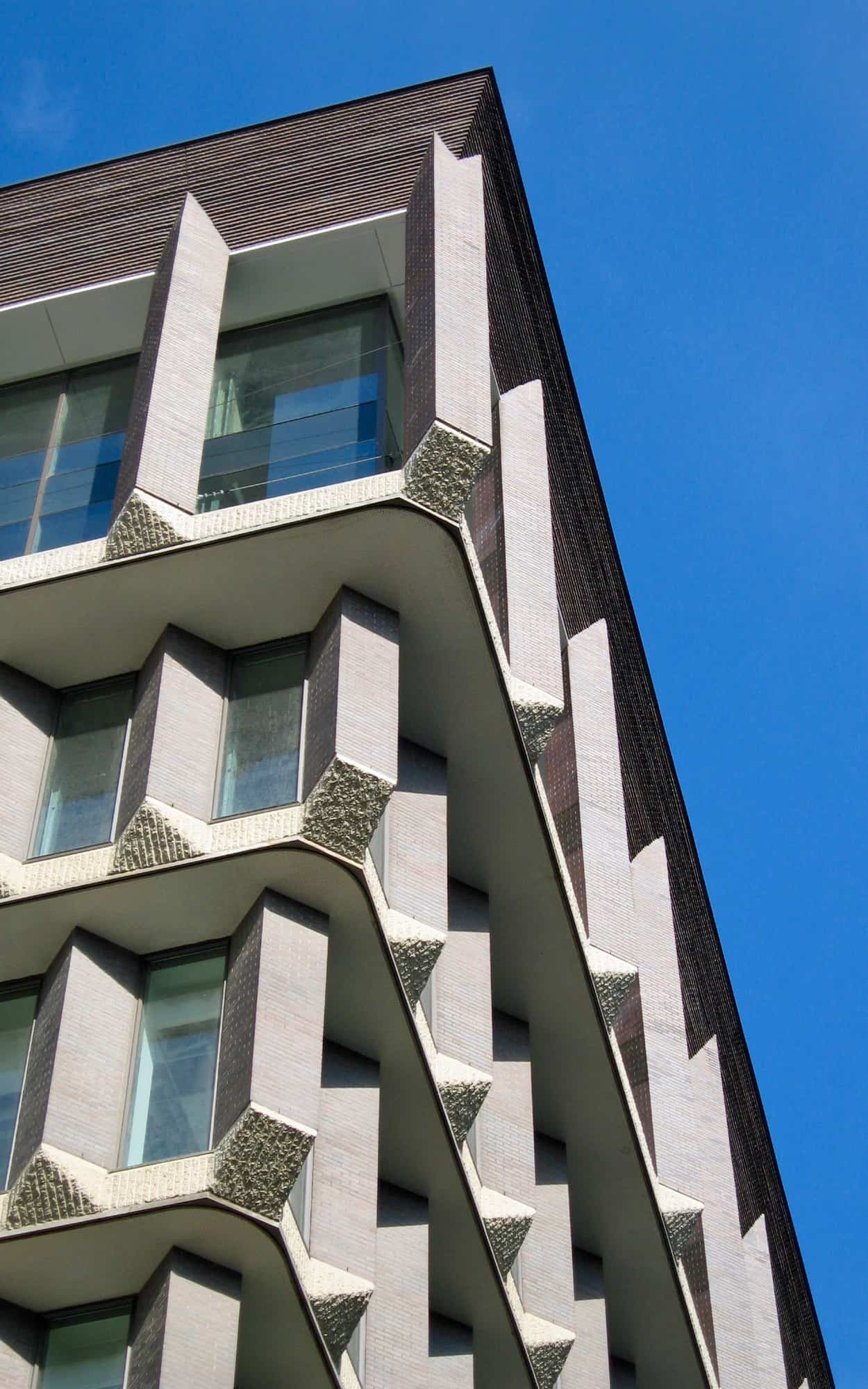 Detail highlighting the concrete and brick detailing near the top of the building