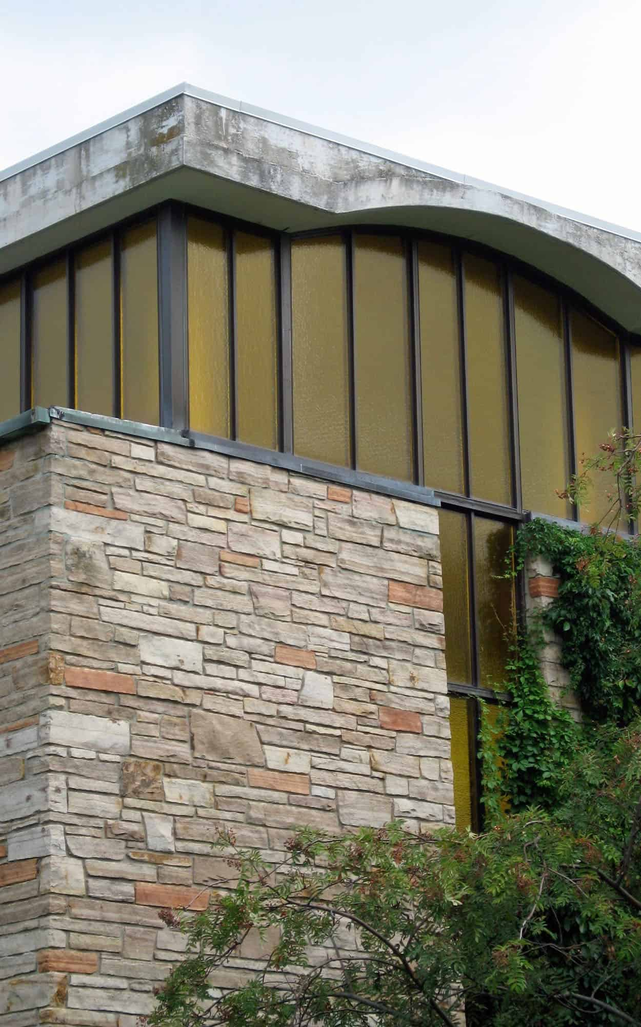 Corner detail of the chapel with its floating concrete roof amber clerestory windows and quarry faced sandstone walls