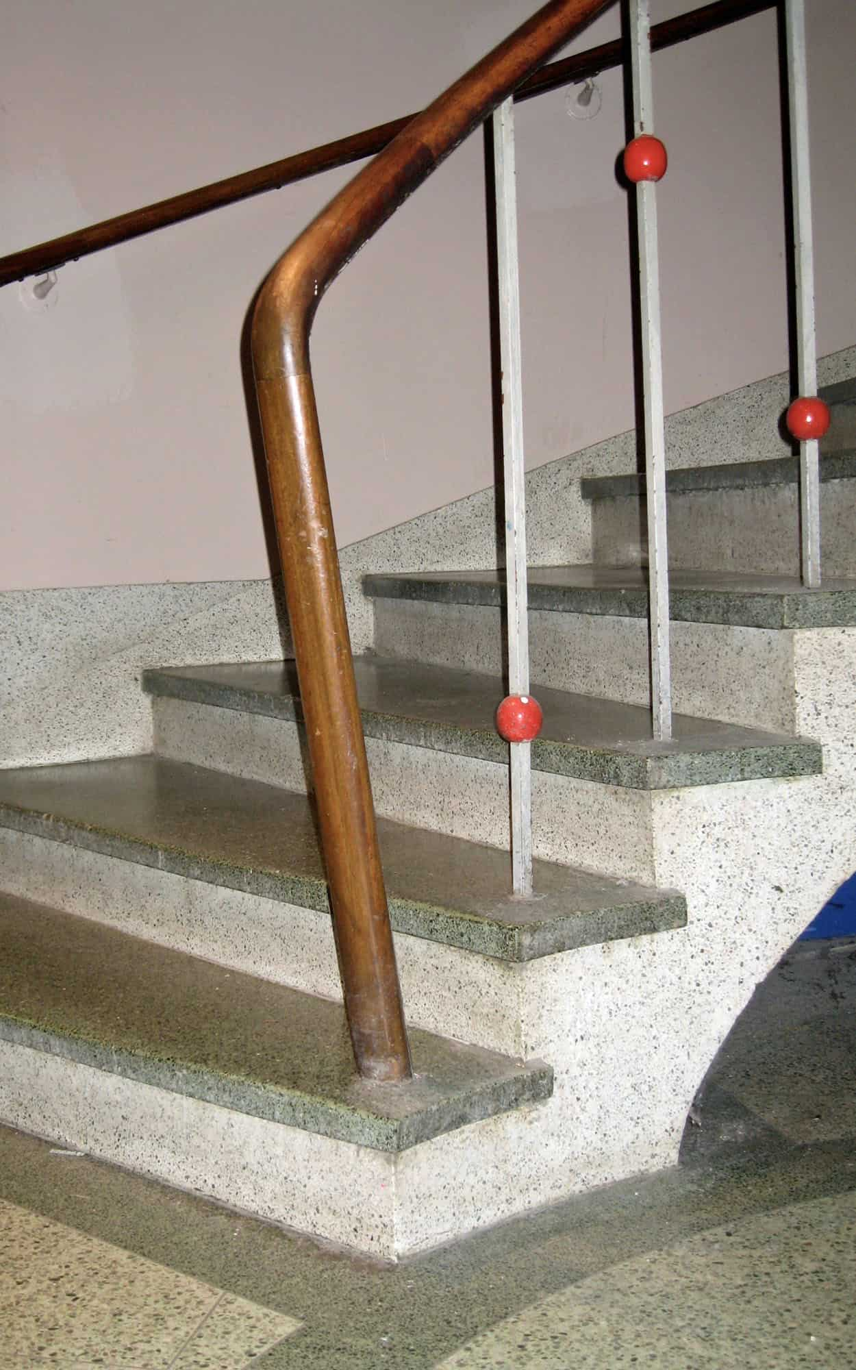 Detail of terrazzo finishes, wooden handrail and balusters which comprise the dramatic main stair