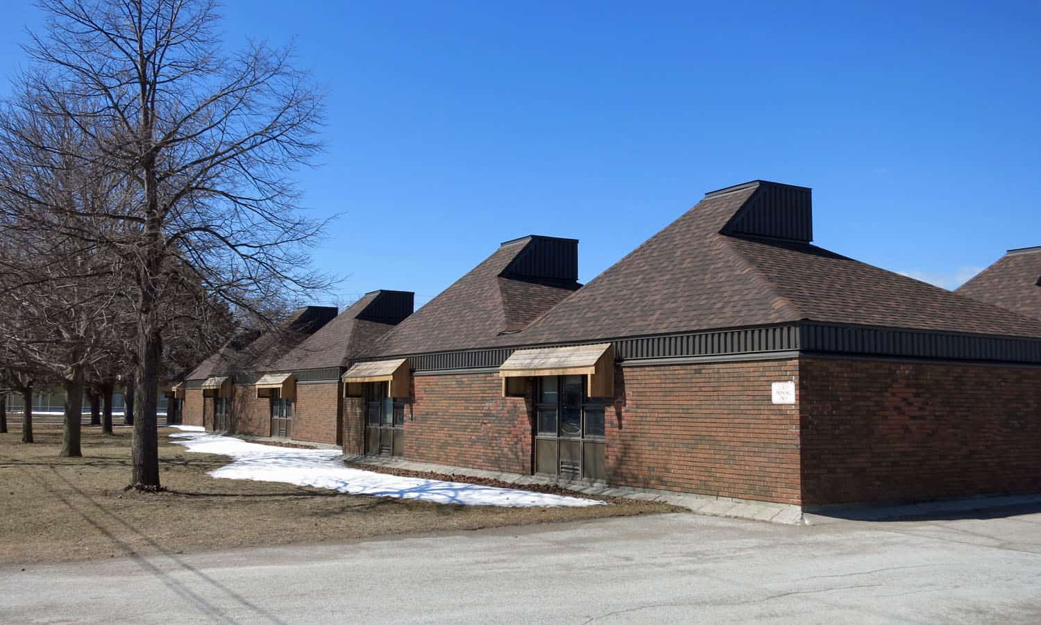 The south elevation with its rhythm of classrooms featuring pyramidal roofs, light monitors (now enclosed), and brick walls